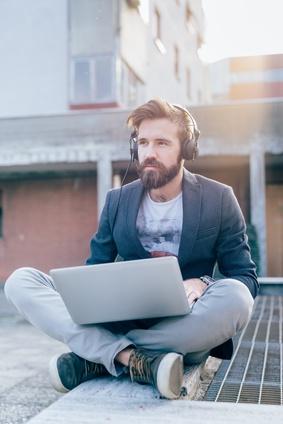 junger Mann sitzt draußen mit Laptop und Kopfhörern