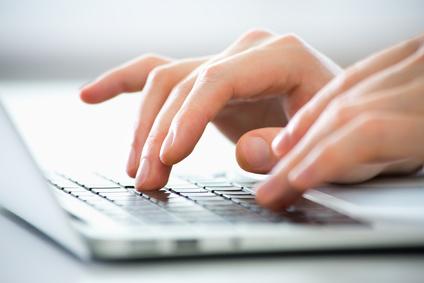 Nahaufnahme einer Hand beim Tippen auf einem Laptop